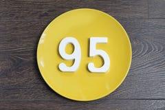 Numerowy dziewięćdziesiąt pięć na żółtym talerzu Obraz Royalty Free