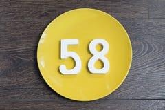 Numerowy pięćdziesiąt osiem na żółtym talerzu Obrazy Royalty Free