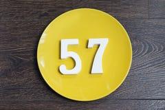 Numerowy pięćdziesiąt siedem na żółtym talerzu Zdjęcia Royalty Free