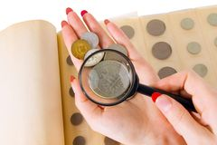 Numismatics. The female hands holding a magnifier and coins from an album of the collector of coins Stock Images