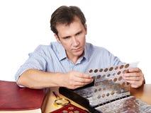 Numismatist человека рассматривает его собрание монетки Стоковые Изображения RF