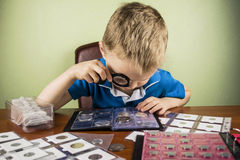 Numismatist. Boy looking through a magnifying glass at the old coin numismatist Royalty Free Stock Images
