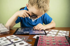 Numismatist. Boy looking through a magnifying glass at the old coin numismatist Stock Images