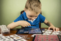 Numismatist. Boy looking through a magnifying glass at the old coin numismatist Royalty Free Stock Photography