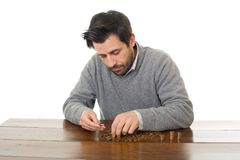 Numismatist. Man examines coins on a desk, isolated Stock Photo