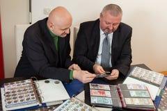 2 numismatists рассматривают собрание монетки Стоковое Изображение RF