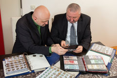 2 numismatists рассматривают собрание монетки Стоковая Фотография
