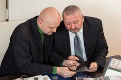 2 numismatists рассматривают собрание монетки Стоковое Изображение