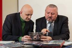 2 numismatists рассматривают собрание монетки Стоковое фото RF