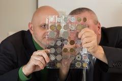 2 numismatists рассматривают собрание монетки Стоковая Фотография RF