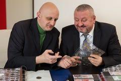 2 numismatists рассматривают собрание монетки Стоковые Изображения