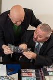 2 numismatists рассматривают собрание монетки Стоковые Изображения RF