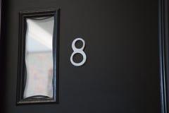 Nummer åtta på modern design för svart dörrbakgrund Arkivbilder