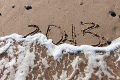 Nummer 2013 op strandzand met golfwater Stock Afbeeldingen