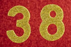 Nummer achtendertig gouden kleur over een rode achtergrond Anniversar Royalty-vrije Stock Afbeelding