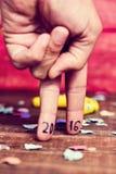 Nummer 2016, als nieuw jaar, in de vingers van een jonge mens Stock Foto's