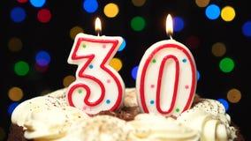 Nummer 30 bovenop cake - dertig verjaardagskaars het branden - slag uit aan het eind Kleur vage achtergrond stock videobeelden