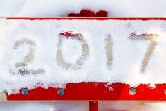 Nummer 2017 in de sneeuw op de rode schommeling voor kinderen Royalty-vrije Stock Foto's