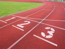 Nummer ett och nummer två, röd rubber rinnande löparbana Royaltyfri Bild