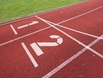 Nummer ett och nummer två, röd rubber rinnande löparbana Arkivfoton