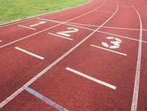Nummer ett och nummer två, röd rubber rinnande löparbana Arkivfoto