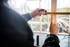 Nummer för hand för snickare` s rörande på måttband på platsen Royaltyfria Foton