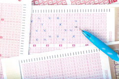 Nummer för markering för hand för person` s på lottsedel med pennan segra Royaltyfria Foton