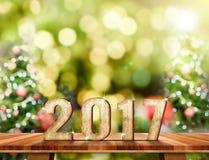 Nummer för nytt år 2017 på brun Wood tabellöverkant med abstrakt suddighet Arkivfoton