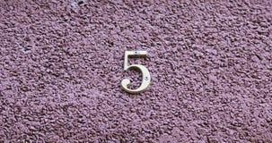 Nummer fem på väggen av ett hus Arkivfoto