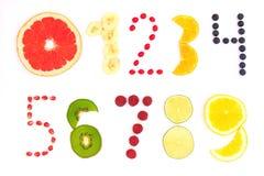 Nummer från noll till nio gjorde av frukt och bär på vit bakgrund Arkivbild