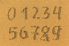 Nummer från 0 till 9 som är utdragna på sanden till havet Utbildning Arkivfoton