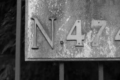 Nummer fyra och sju eller fyrtiosju med bokstav N på ett tecken eller en bruten plattamonokrom Royaltyfria Bilder