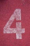 Nummer fyra på rinnande spår Vitt spårnummer på röd rubber löparbana Arkivbilder
