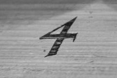 Nummer fyra som brännmärkas i trä Arkivfoto