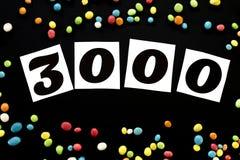 Nummer 3000 met multicolored suikergoed rond op zwarte achtergrond Stock Fotografie
