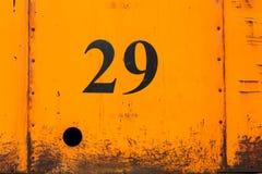 Nummer 29 på den rostiga orange plattan för metallark med hålet Fotografering för Bildbyråer
