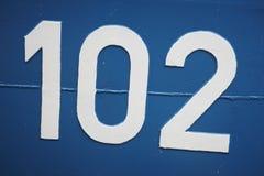 Nummer 102 på en metallisk blåttyttersida. Arkivbilder