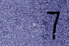 Nummer sju på den blåa grungy cementväggen Royaltyfri Fotografi