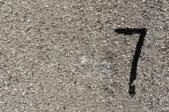 Nummer sju på den grungy cementväggen Arkivbilder