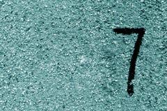 Nummer sju på den grungy cyan tonade cementväggen Royaltyfria Bilder