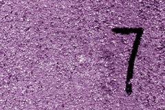 Nummer sju på den purpurfärgade grungy cementväggen Arkivbilder