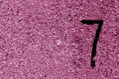 Nummer sju på den rosa grungy cementväggen Royaltyfri Fotografi