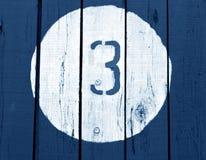 Nummer tre på den träblått tonade väggen Royaltyfria Bilder