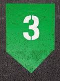 Nummer tre som stencileras i vit målarfärg på en grön geometrisk symb Royaltyfri Foto
