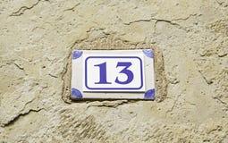 Nummer tretton på en vägg Arkivbild