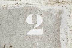 Nummer twee door een bakstenen muur Stock Foto
