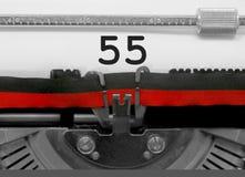Nummer 55 vid den gamla skrivmaskinen på vitbok royaltyfri bild