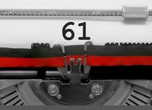 Nummer 61 vid den gamla skrivmaskinen på vitbok Royaltyfria Foton
