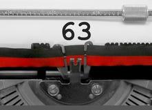 Nummer 63 vid den gamla skrivmaskinen på vitbok Arkivbild