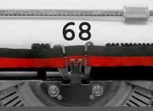 Nummer 68 vid den gamla skrivmaskinen på vitbok Royaltyfria Bilder